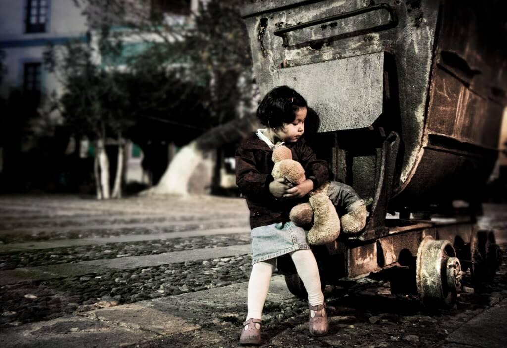 Una bambina che abbraccia un'orsacchiotto