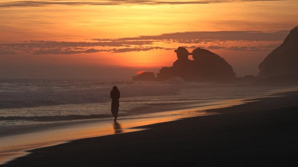 Uomo che cammina in una spiaggia dell'oceano pacifico al tramonto
