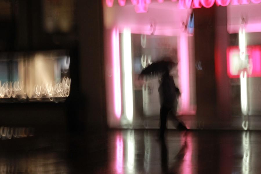 Foto mossa di uomo sotto la pioggia davanti a insegne al neon
