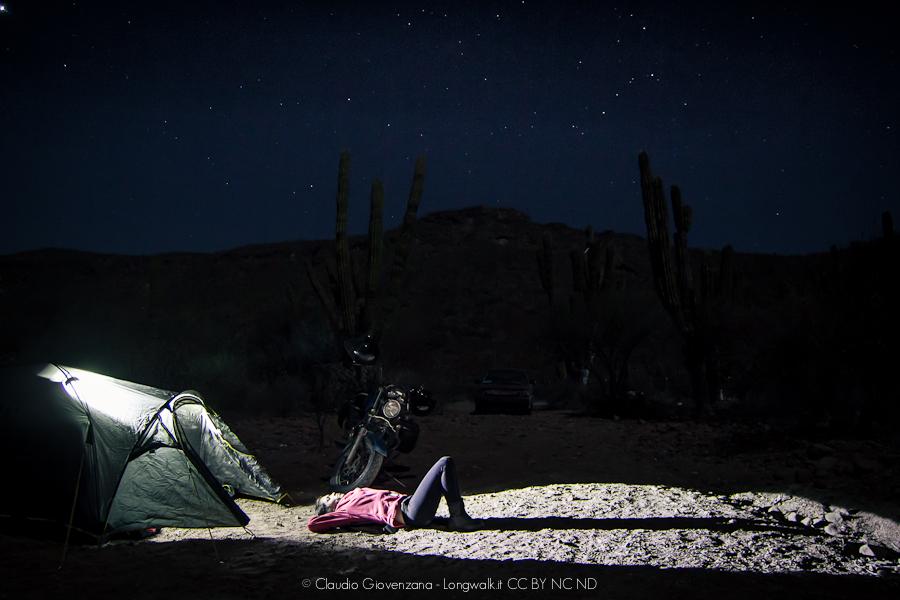 Accampamento in tenda nella Bassa California, la motoguzzi e una ragazza sotto le stelle.