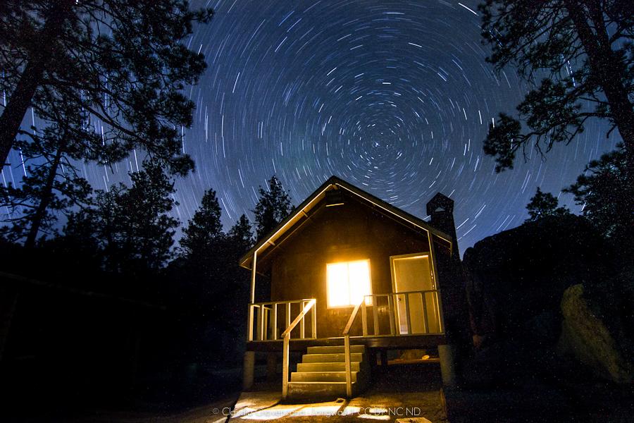 Una casa nel bosco sotto una volta stellare in movimento