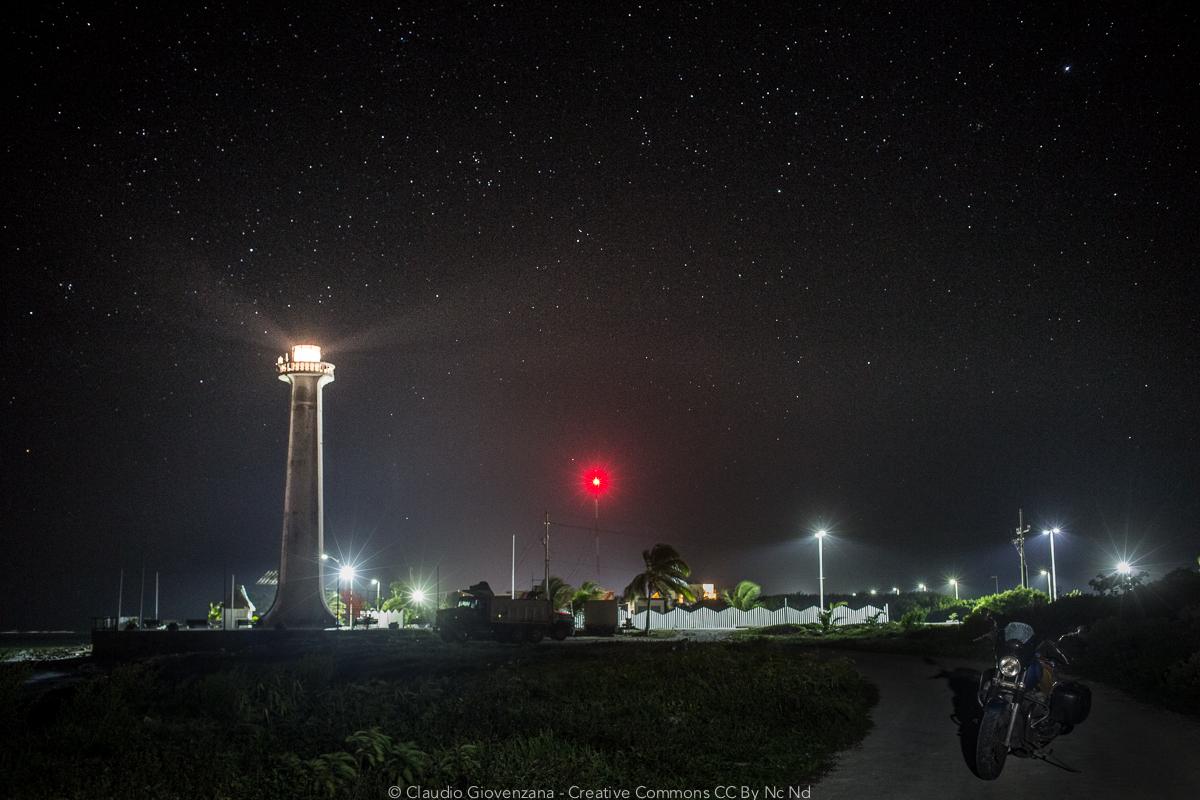 Motoguzzi di notte vicino a un faro sotto le stelle