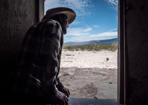 Un uomo che si sporge dalla sua casa nel deserto del nord del Messico